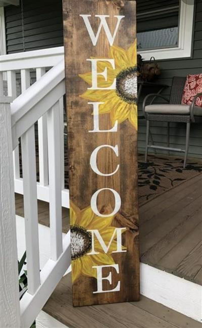 "wooden board with sunflowers and the word ""welcome"""